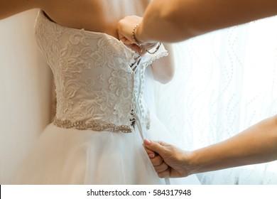 Hands of bridesmaid helping blonde bride to wear her wedding dress