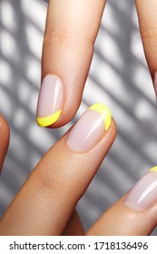 Hands with bright yellow french manicure on geometric background. Nails art design. Close-up of female hands with trendy neon nails on silver striped print background