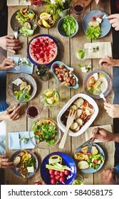 Hands of buddies eating vegetarian food by dinner