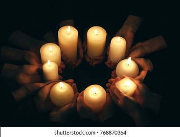 Hands with burning candles on dark background