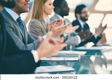 Hands of business partners applauding to reporter after listening to presentation at seminar, blurry