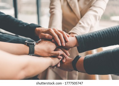 Hands of business people come together in a stack of hands to symbolize collaboration, teamwork to achieve goals and success. - Shutterstock ID 1777505747