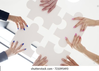 Hands of business people holding white puzzle