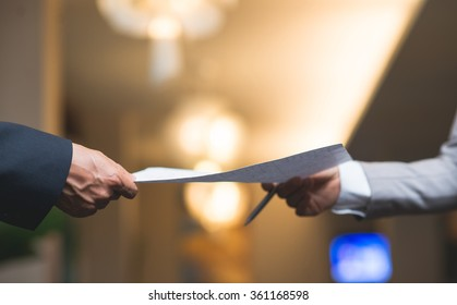Hands of business people passing document