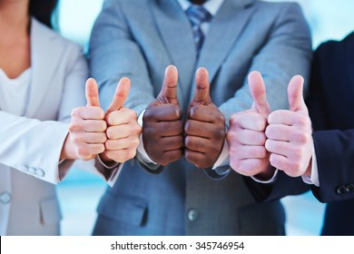 Hands of business people showing thumbs up