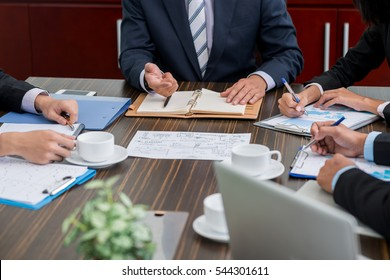 Hands of business people working with documents at meeting