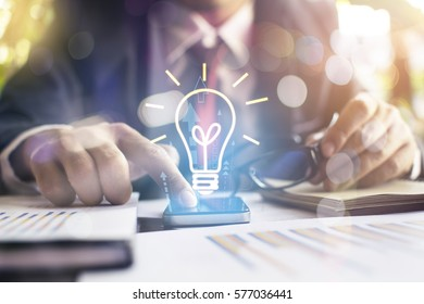 Hands of business person holding illuminated light bulb sign