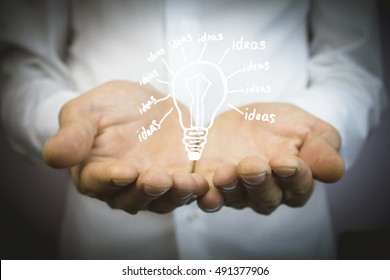 Hands of business person holding light bulb