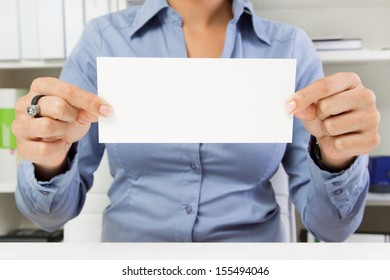 Hands of business woman in blue holding blank white sign
