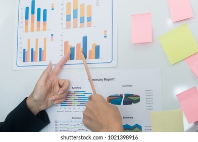Hand's business woman holding pencil pointing at analyzing market data to clients or partners have been informed on white board,Equities the charts and summary info show about fixed Income,