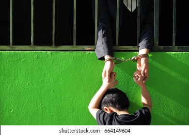 hands of business woman in jail holding with her son outside