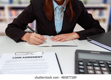 Hands of business woman writing on notebook with calculator and loan agreement at office desk