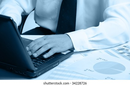 Hands of the businessman above the keyboard laptop. Blue color