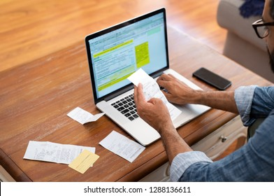 Hands of businessman analyzing invoice on laptop while checking bills. Rear view of latin man checking invoice while matching them on computer. Closeup of man hands calculating financial expenses.