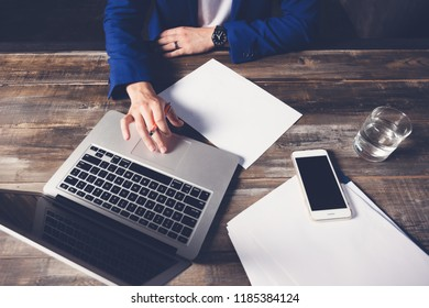 Hands of a businessman in a blue suit in a clock on top, a laptop, sheets of paper, a phone, a glass of water on a wooden table. Business concept