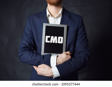 In the hands of a businessman a frame with the inscription:CMO