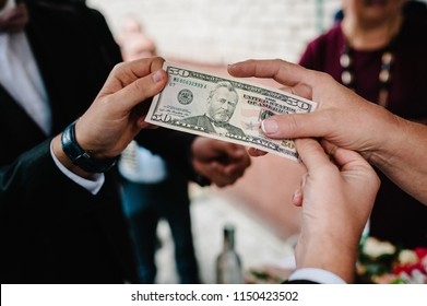 Hands of businessman give money exchange to business woman, holding US dollar, USD. bills, offers dollar bank note. cash in business, bribery and corruption concept. Paying compensation to partners.