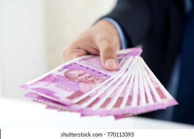 Hands of businessman holding money, Indian Rupee currency, paying cash for the business investment