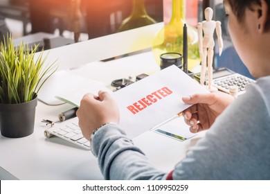 hands of Businessman holding Rejection Letter on desktop at home office . selective focus