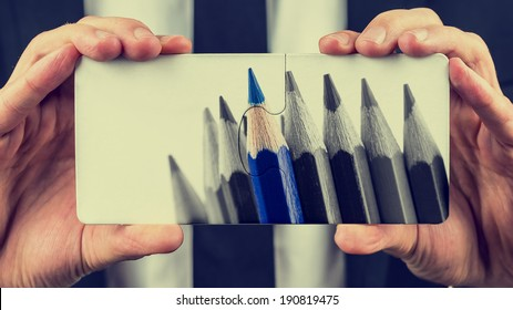 Hands of a businessman holding two puzzle pieces depicting a greyscale image of colored pencils with one blue pencil standing out from the others in a leadership and individuality concept.
