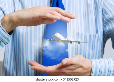 Hands of businessman and model of flying airplane