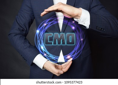 In the hands of a businessman, a neon circle with the inscription:CMO