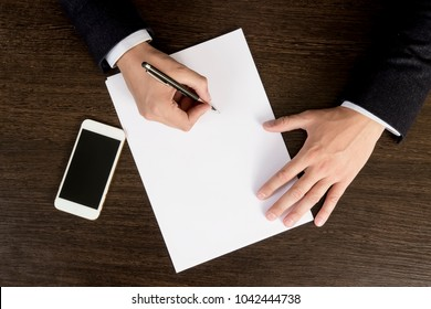Hands of businessman on the desktop sign papers. The top view of the workflow in the office of the company. Sign the contract. Signing of a major transaction