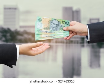 Hands of businessman passing Australian dollar (AUD) banknote with blurred office building background.