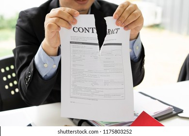 Hands of businessman ripping contract agreement paper,contract canceled,break the rules - failure business concept.