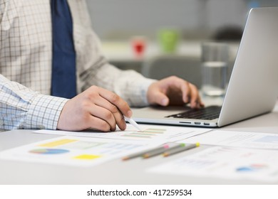 Hands of Businessman in Shirt and Tie working on Laptop Computer and pointing on printed Data Charts with some stationery and red Coffee Cup