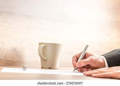 Hands of a businessman writing with a silver pen on a paper sheet, at a wooden desk, next to a mug of coffee or cappuccino, with copy space on blurred beige wall.