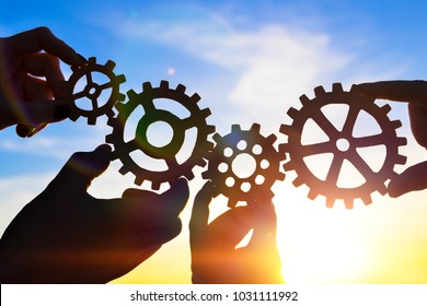The hands of businessmen connect the gears with a puzzle, against the background of the sun's rays. Business concept, idea, teamwork. Strategy, cooperation, creative.