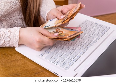 Hands of businesswoman counting euro banknotes on laptop keyboard