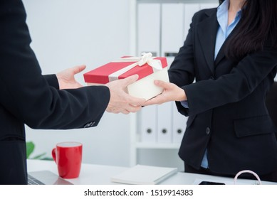 Hands of businesswoman giving christmas gift to her boss in office.