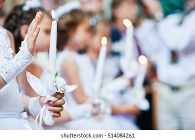 Hands with candles of little girls on first holy communion