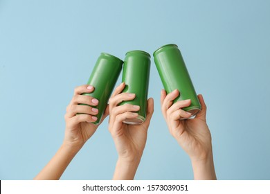 Hands with cans of beer on color background