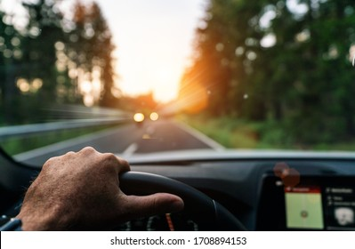 Hands of car driver on steering wheel, fast driving car at spring day on a country road, having fun driving the empty highway on tour journey - POV first person view shot