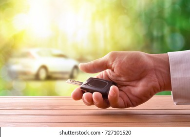 Hands with car keys on a wooden table with car image on nature background. Concept of car purchase