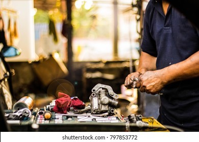 Hands of car mechanic in auto repair service in car service garage.