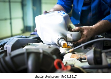 Hands of car mechanic with a bottle of engine oil, in auto repair service, oil and filter changing maintains