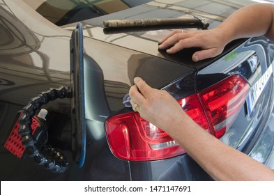Hands of car mechanic in car service with tools for repairing dents in car body.