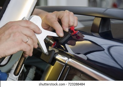 Hands of car mechanic in the car service with tools for repairing dents