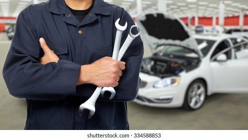 Hands of car mechanic with wrench in auto repair service.