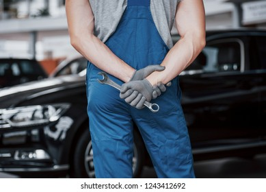 Hands of car mechanic with wrench in garage.