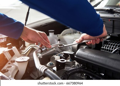 Hands of car mechanic with wrench in garage