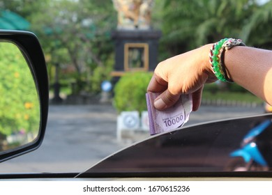 hands from the car paying Indonesian money for toll