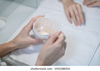 Hands care. Close up picture of beauticia apllying some cream to the clients hands