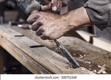Hands of carpenter with chisel in the hands on the workbench in carpentry