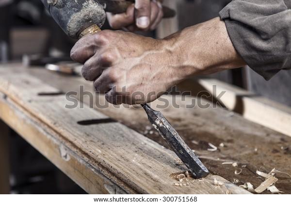 Handschuhe des Zimmermanns mit Kapselhülle in den Händen auf der Werkbank in Tischlerei