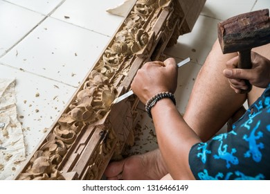 Hands of a carpenter making traditional wood  carving in Bali, Indonesia. Local craftmanship tradition concept